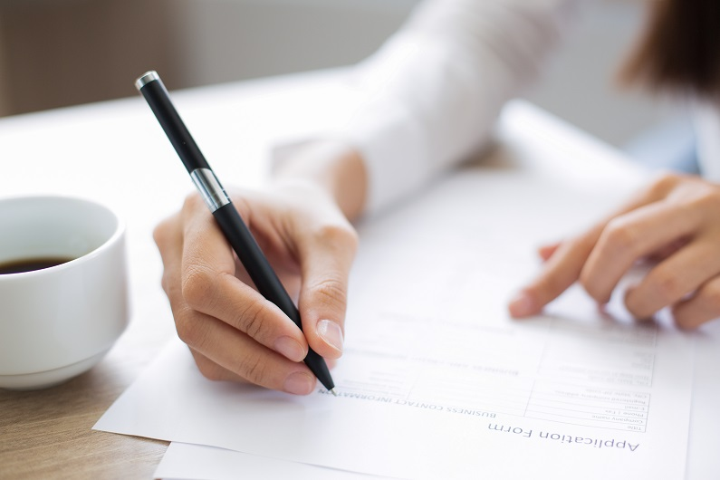 person holding a pen and completing an application form
